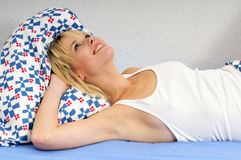 Happy blond woman lying in bed daydreaming Stock Image