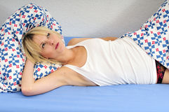 Happy blond woman lying in bed daydreaming Stock Images
