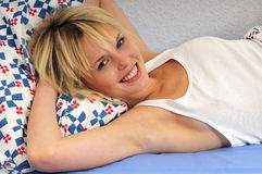 Happy blond woman lying in bed smiling Royalty Free Stock Image