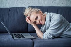 Happy blond woman lying prone on sofa and working on laptop computer stock image