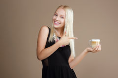 Happy Blond Woman Points Out to the Cup of Coffee Stock Images