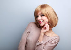 Happy blond woman with short hair style looking with hand near f Stock Photos