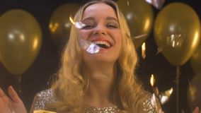 Happy blond woman standing under falling confetti, enjoying party, celebration. Stock footage stock video footage