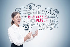 Happy blond woman with a tablet, business plan Stock Photography