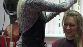 Happy blond woman talk with her personal hair stylist while making haircut. 4K stock video
