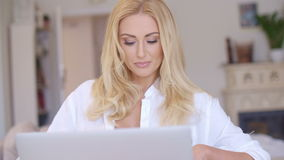 Happy Blond Woman Using her Laptop Computer. Close up Happy Young Blond Woman in White Shirt Using her Laptop Computer While at the Living Room stock video