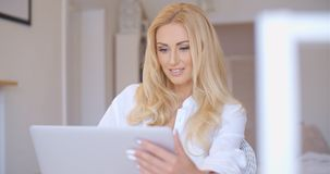 Happy Blond Woman Using her Laptop Computer Royalty Free Stock Image
