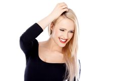 Happy Blond Woman Wearing Black Long Sleeve Shirt. Close up Happy Young Blond Woman Wearing Elegant Black Long Sleeve Shirt with One Hand on her Hair. Isolated Royalty Free Stock Images