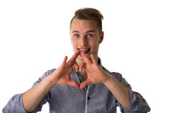 Happy blond young man doing heart or love sign wit Stock Image