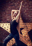 Happy blond young slim woman dancing in blue ripped jeans on yel Royalty Free Stock Photos