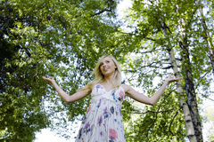 Happy blond young woman in park smiling Stock Photos
