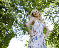 Happy blond young woman in park smiling Royalty Free Stock Photography