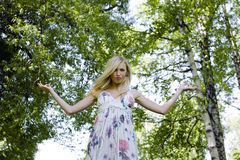 Happy blond young woman in park smiling Royalty Free Stock Images