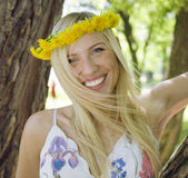 Happy blond young woman in park smiling. Floral close up Royalty Free Stock Photography