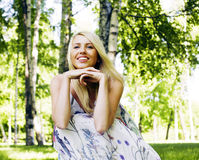 Happy blond young woman in park smiling, floral close up. Lifestyle people Royalty Free Stock Photos