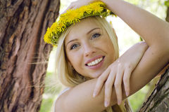 Happy blond young woman in park smiling. Floral close up positive Royalty Free Stock Photo
