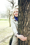Happy blond young woman in park smiling, hugging tree, lifestyle people concept. Close up Stock Photography
