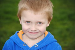 Happy blonde boy. Happy little caucasian boy in the park royalty free stock image