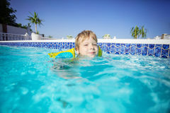 Happy blonde boy wearing floaties and swimming outdoors. Happy blonde boy wearing floaties and swimming in outdoor pool Stock Photo