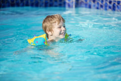 Happy blonde boy wearing floaties and swimming in pool. Happy blonde boy wearing floaties and swimming in outdoor pool Stock Images