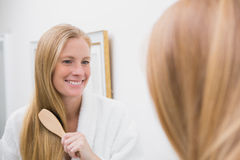 Happy blonde brushing her hair Royalty Free Stock Image