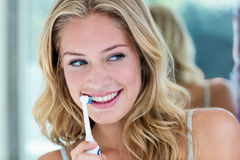 Happy blonde brushing her teeth in the bathroom. At home Royalty Free Stock Photo