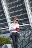 Happy blonde business woman in sunglasses with notebook against of modern building royalty free stock images