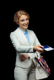 Happy blonde businesswoman with passport and air ticket in white suit ready to trip. On black Royalty Free Stock Photography