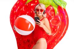 Free Happy Blonde Caucasian Female Lies In Swimsuit With Big Rubber Mattress And Colourful Ball, Earphones And Smiles Royalty Free Stock Image - 163850086
