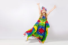 Happy blonde child girl in hippie colorful dress against white wall.  stock image