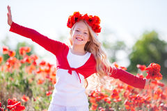 Happy blonde child girl in spring field with poppies Royalty Free Stock Photography