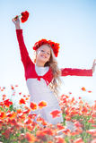 Happy blonde child girl in spring field with poppies Stock Image