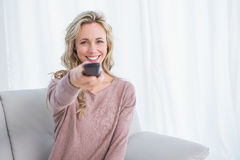 Happy blonde on couch changing tv channel Stock Image