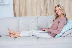Happy blonde on couch relaxing and using laptop Stock Image