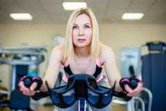 Happy blonde doing indoor biking in a fitness club. Happy blonde doing indoor biking in a fitness club Royalty Free Stock Image