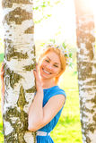 Happy blonde embracing birch trunk in the park Royalty Free Stock Photos