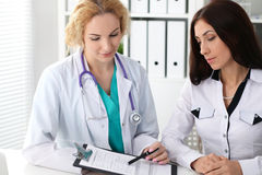 Happy blonde female doctor and patient discussing medical examination results. Medicine, healthcare and help concept royalty free stock images