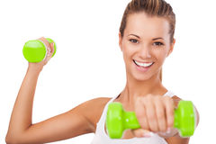 Happy blonde female exercising with weights Royalty Free Stock Photography