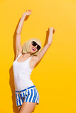 Happy blonde girl in black sunglasses with arms raised Stock Photos
