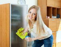Happy blonde girl cleaning  glass Royalty Free Stock Photo