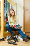 Happy blonde girl cleaning shoes Royalty Free Stock Images