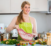 Happy blonde girl cooking ribs at home Royalty Free Stock Photos