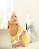 Happy blonde girl with credit card and notebook. Online shopping Royalty Free Stock Image
