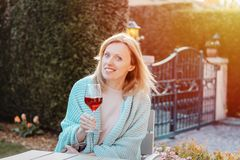 Happy blonde girl enjoying red wine outdoors. Smiling attractive joyful woman in light blue knitted plaid smiling and looking at g royalty free stock photos