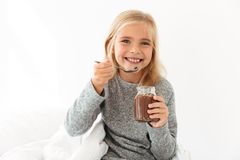 Happy blonde girl in gray pajamas holding glass jar and spoon wi Royalty Free Stock Images