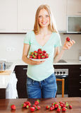 Happy blonde girl holding  heap of strawberries Stock Photos