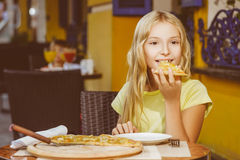Happy blonde girl indoors eating pizza smiling Royalty Free Stock Images