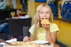 Happy blonde girl indoors eating pizza smiling Royalty Free Stock Photos