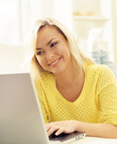 Happy blonde girl with notebook at home. Online shopping, laptop Royalty Free Stock Photos