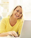 Happy blonde girl with notebook at home. Online shopping, laptop Royalty Free Stock Images